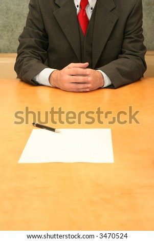 Business-man sitting at the desk, open contract infront of him. - stock photo