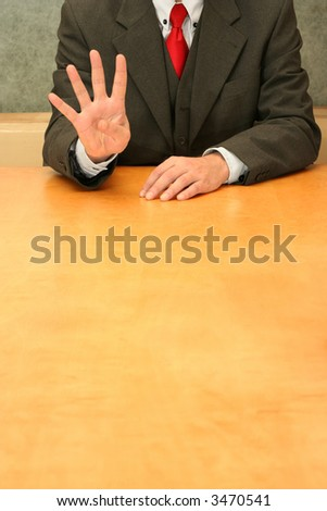 Business-man sitting at the desk, showing number four. - stock photo