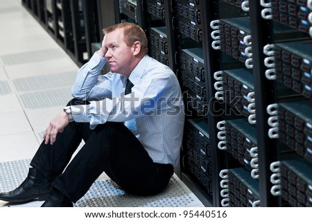 Business man sitting in a data center looking frustrated with the current system. He is looking for a better IT solution - stock photo