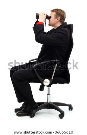 Business man sitting in chair and searching with binoculars