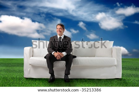 business man sitting on a sofa in a grass field