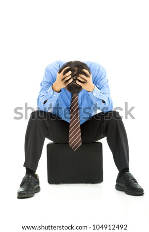 business man sitting on briefcase with headache - stock photo