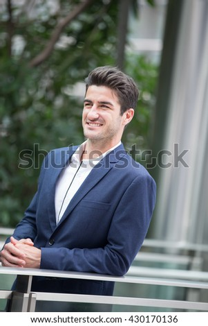 Business man smile with business office building background, caucasian, shot in Hong Kong