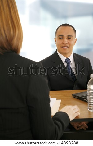 business man smiling and talking to business woman. focus on the man. concept for team work, business related, selling, or meeting