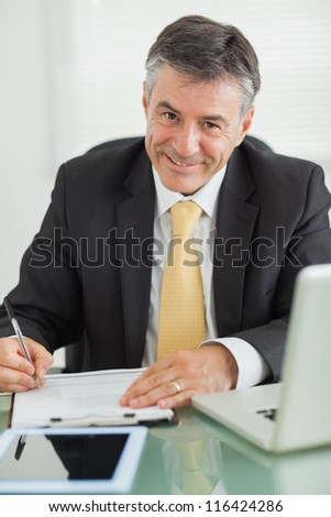 Business man smiling while working in his office - stock photo