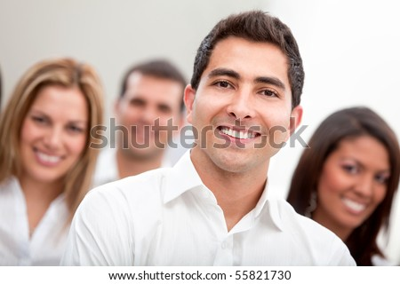 Business man smiling with a group behind at the office - stock photo
