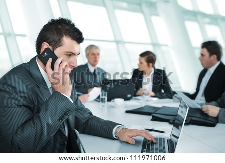 Business man speaking on the phone during meeting - stock photo
