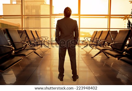 Business man standing in airport hall waiting his flight. Beautiful view of lonely male passenger looking through glass window in airport terminal.   - stock photo
