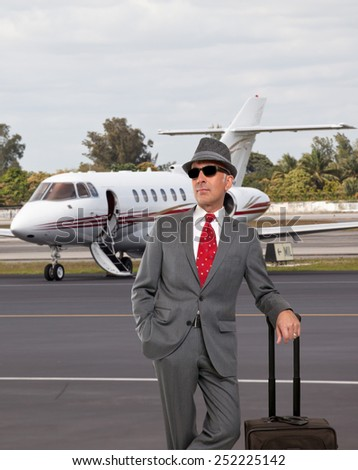 Business man standing next to private jet  - stock photo