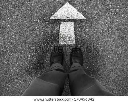 Business man standing on ground with arrow pointing the direction to go