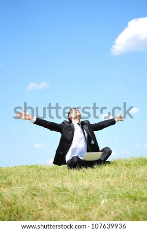 Business man standing on laptop in nature - stock photo