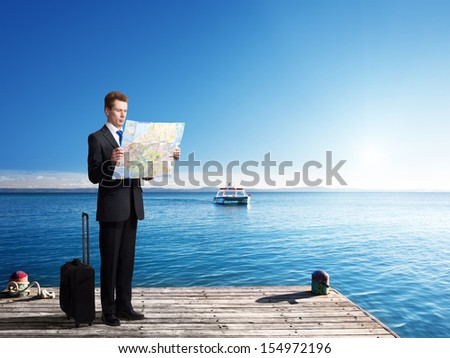 Business man standing on pier with map in hands - stock photo