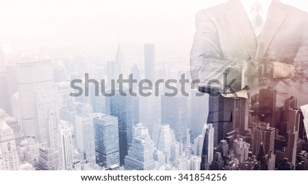 Business man standing on roof with city view in the background - stock photo