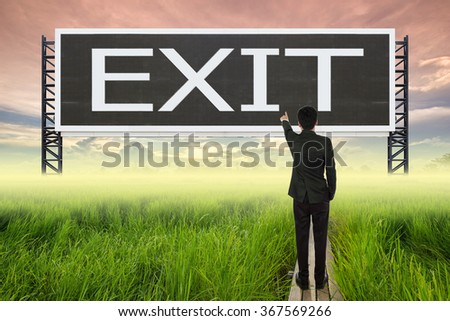 business man standing on wood bridge between rice field and pointing with large sign of exit (business concept)