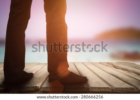 business man standing on wooden floor and sea side background - stock photo