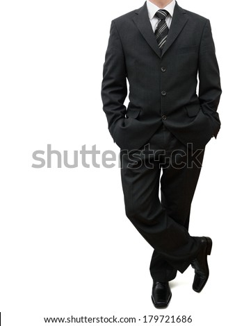 business man standing with legs crossed and both hands in his pockets - stock photo