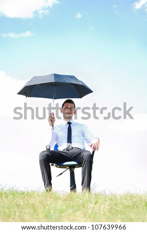Business man standing with umbrella in nature