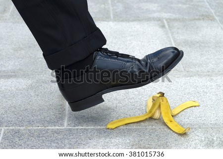 Business man stepping on banana skin peel, work accident concept - stock photo
