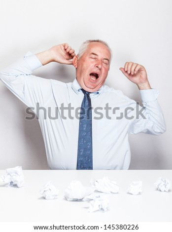 Business man stretching his arms while yawning - stock photo