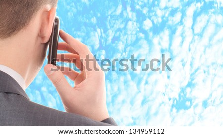business man talking on a mobile phone on blue cloudy sky background - stock photo