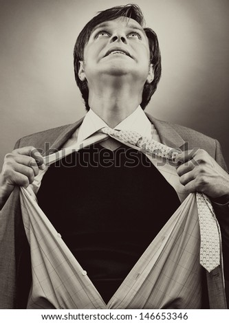 Business man tearing off his shirt over gray background. Monochrome portrait - stock photo