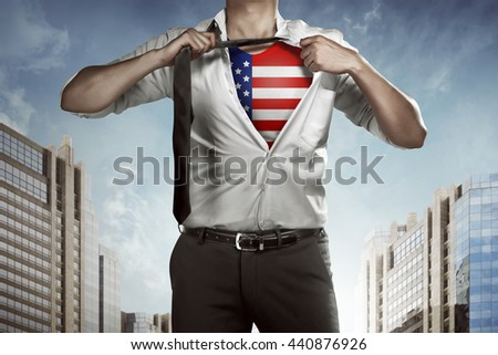 Business man tears open his shirt with american flag in a super hero fashion getting ready to save the day. 4th of July concept - stock photo
