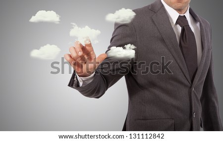business man touching cloud structure, grey background - stock photo