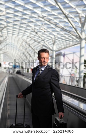 business man travel with bag and trolley on escalators - stock photo