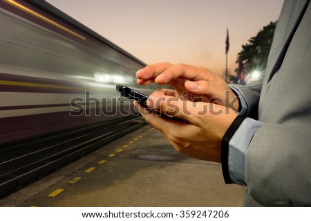 Business Man use Mobile Phone in Railway Station at Dawn with High Speed running Train - stock photo