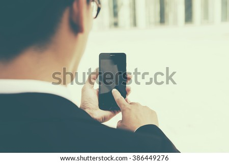 Business man using a variety of mobile devices, mobile phones, smart watches, tablet, computer - stock photo