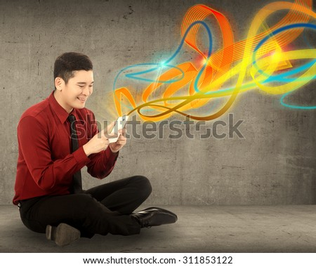 Business man using cellphone with ray of light out from device - stock photo
