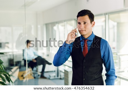 Business man using his mobile phone in office