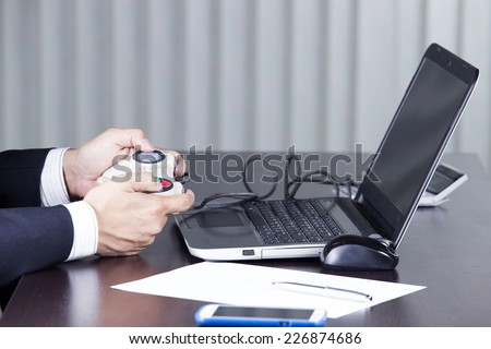 Business man using  joystick playing a video game  - stock photo