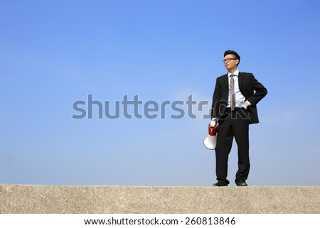 business man using megaphone shouting with blue sky background, asian