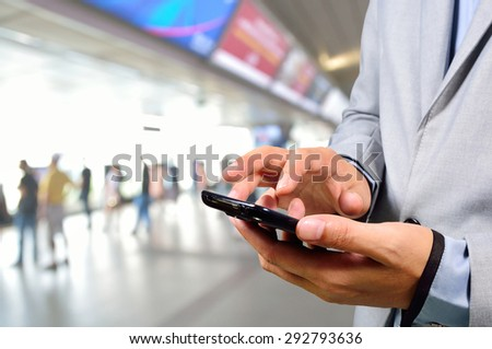 Business Man using Mobile Phone in Modern Train Station or Subway station - stock photo