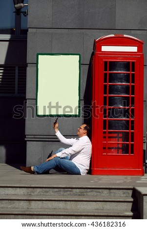 Business man using mobile phone red classic English telephone box