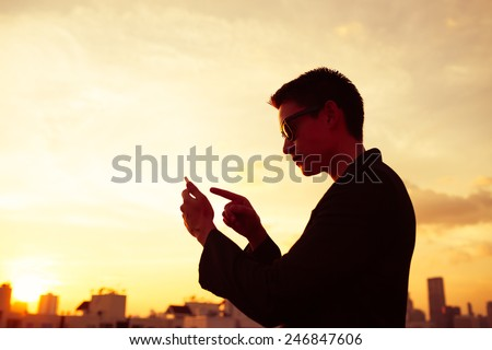 Business man using smart phone in the city - stock photo