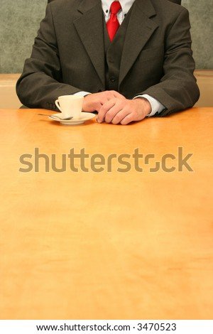 Business-man waiting at the desk, cup of coffee. - stock photo