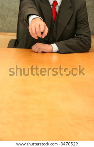 Business-man waiting sitting at the desk pointing on you. - stock photo