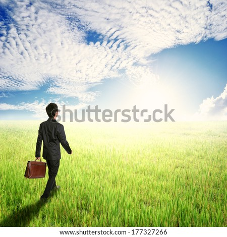 Business man walking and holding bag in fields and sun sky