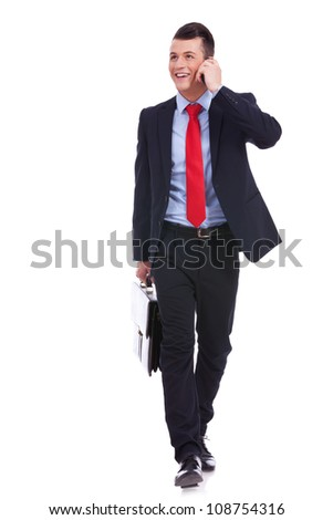 Business man Walking forward and looking to a side while talking on the phone and carying a briefcase over white background - stock photo