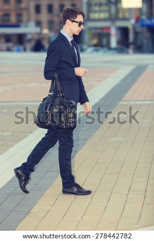 Business man walking in the city. Business people at rush hour walking in the street. confident business man carries his suit jacket over his shoulder while walking down the sidewalk in the city. - stock photo