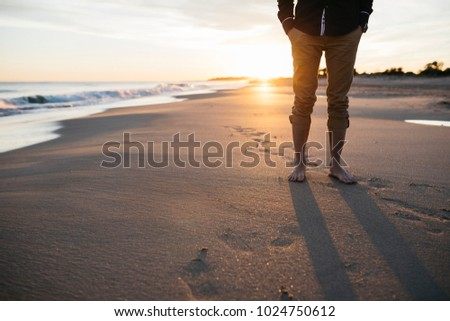 Business man walking on beach at sunset, after work. Free time.