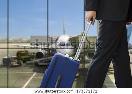 business man walking travel bag by an international airport - stock photo