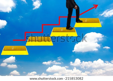business man walking up gold bars stepping ladder have red rising arrow on blue sky  idea concept step by step for success and growth business - stock photo