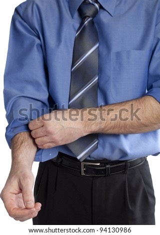 business man wearing a blue shirt and neck tie is rolling up his sleeves - symbolism for getting down to serious work - stock photo