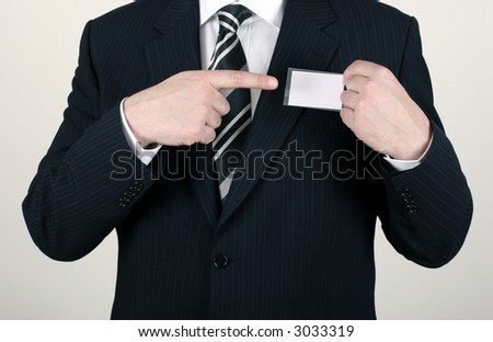 Business man wearing a suit pointing to a blank namebadge - insert your own brand and information - stock photo