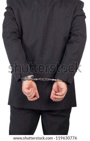 business man with a black suit in handcuffs, back view