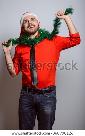 Business man with a Christmas decoration. Winter, corporate party, Christmas hat isolated portrait of a man on a gray background, studio photo.