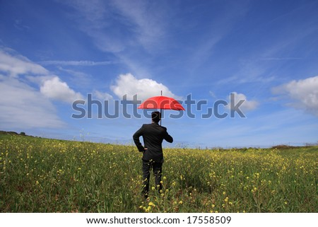 Business man with an open umbrella symbolizing protection on the field - stock photo
